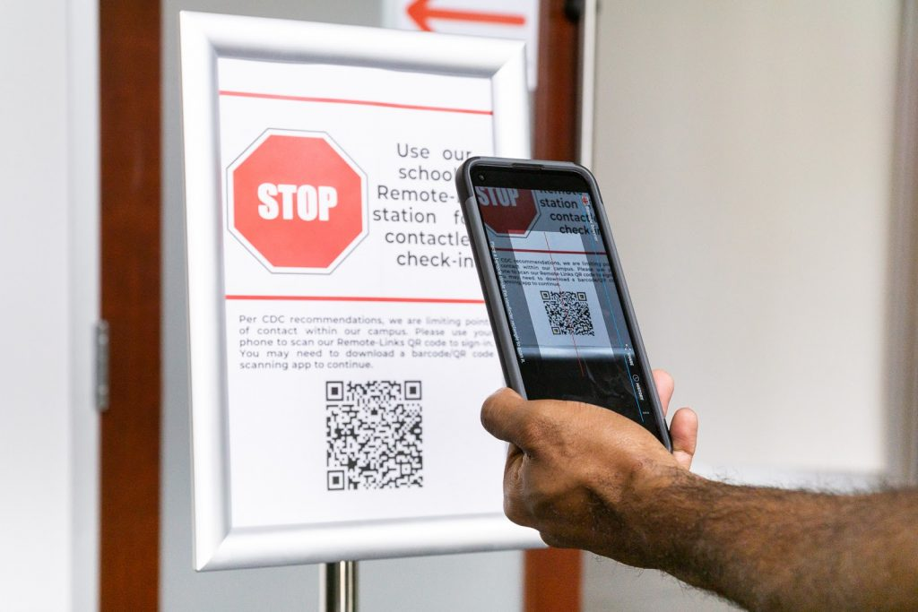 School visitor scanning QR code with cellphone.