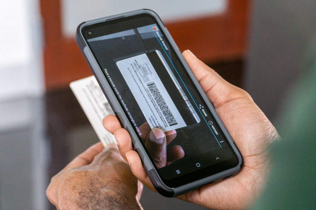 School visitor scanning drivers' license with cellphone.