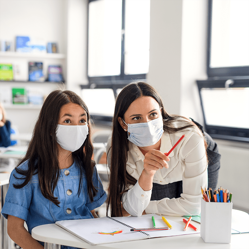 Teacher and child wearing face mask during school.